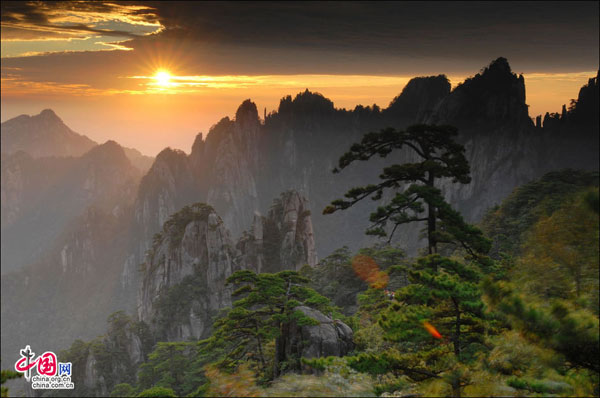 The sun rises from behind the mountain peaks on an early autumn morning at Huangshan Mountain resort. [Photo:China.org.cn]