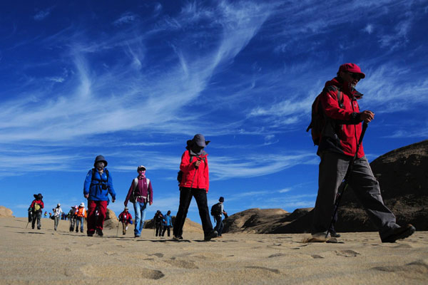 People hike through the desert during an expedition in Da Qaidam, an administrative committee of Northwest China's Qinghai province, on Sept 18, 2012. More than 30 participants will endure gales and exposure to extreme weather during the four days' journey in desert, covering 50 kilometers.(Xinhua Photo/ Li Shaopeng)