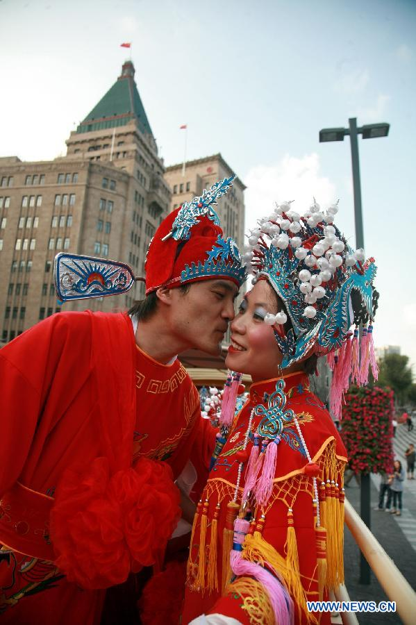 A bridegroom kisses his bride, who wear traditional Chinese costumes, on a tourist double decker bus during a group wedding ceremony held in Shanghai, east China, Sept. 26, 2012. (Xinhua/Zhuang Yi)