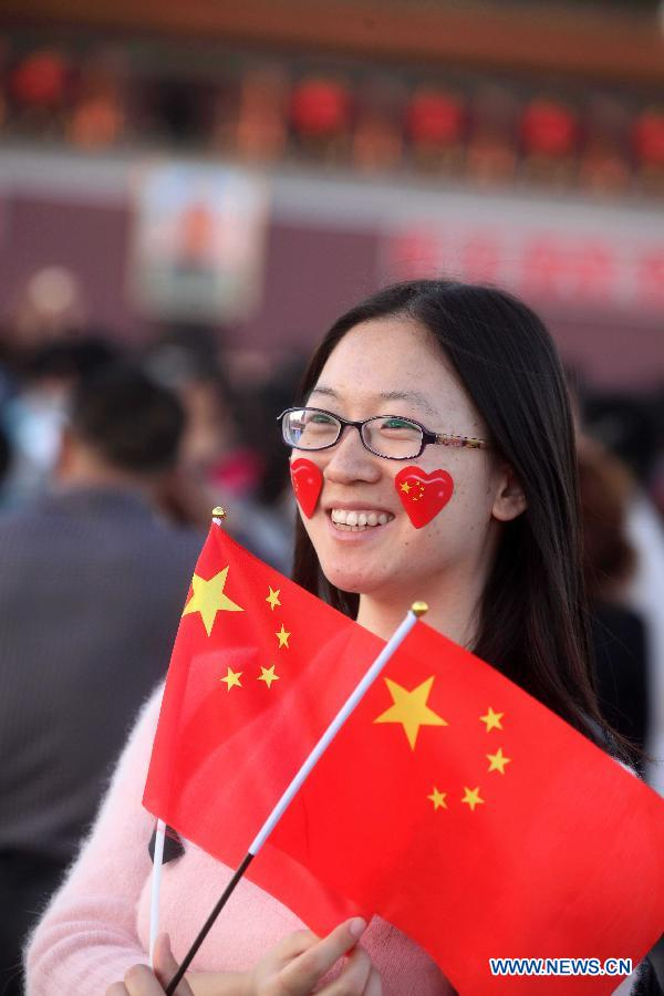 "A tourist holding the national flag visits the Tian'anmen Square in Beijing, capital of China, Sept. 30, 2012. Authorities predicted that around 740 million trips will be made by Chinese people during the eight-day ""Golden Week"" holiday. (Xinhua/Chen Xiaogen)"
