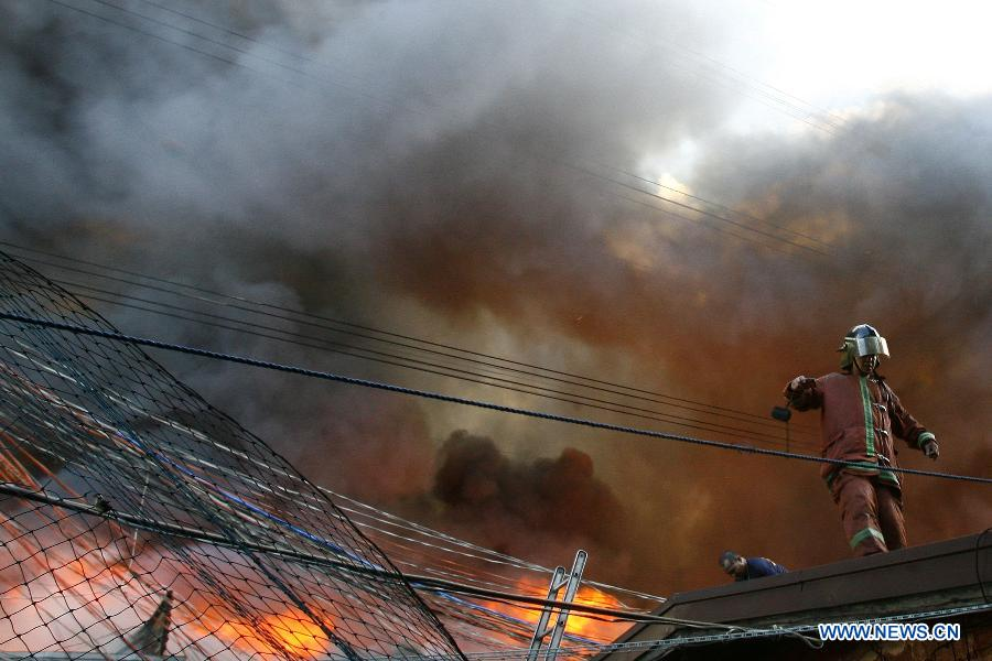 A firefighter stands on the roof of a house as he tries to put out a fire in Quezon City, the Philippines, Oct. 23, 2012. Around 400 houses were razed in the fire, leaving 600 families homeless. (Xinhua/Rouelle Umali)