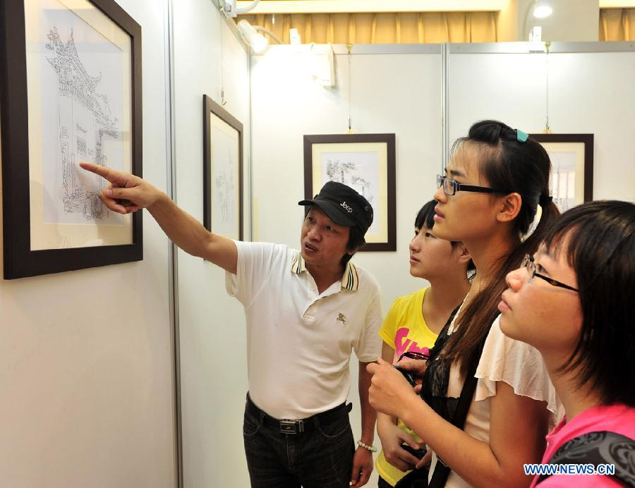 Li Bin (1st L) introduces his works during a solo exhibition held in southeast China's Taiwan.(Xinhua Photo)