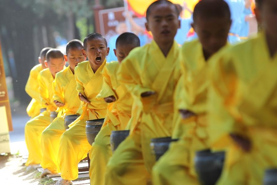 Young students of kungfu school perform during a welcoming ceremony of the 9th Zhengzhou International Shaolin Wushu Festival in Dengfeng City, central China's Henan Province, Oct. 22, 2012. A series of performance as well as Wushu contest and seminar will be held during the festival from Oct. 21 to 25. (Xinhua/Chen Xiaodong)