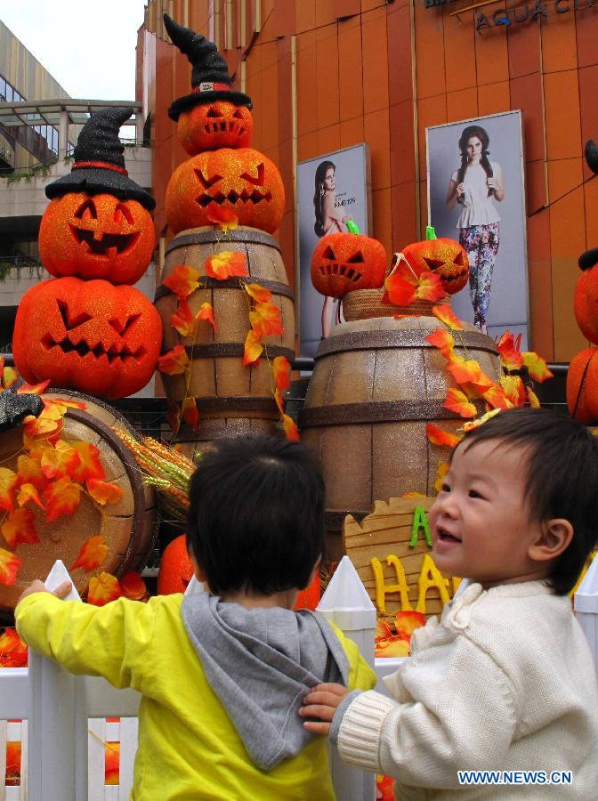 Children play in front of pumpkin-shaped decorations installed at a shopping mall to greet the upcoming Halloween in Nanjing, capital of east China's Jiangsu Province, Oct. 24, 2012. (Xinhua)