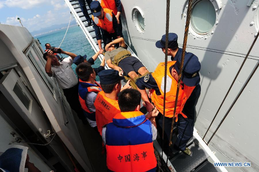 A fisherman injured in a boat sinking accident is transferred to a rescue ship at Sanya port in China's southernmost island province of Hainan, Oct. 24, 2012. A fishing boat sank in the sea off the east coast of Sanya on Tuesday night, and all the 16 fishermen were rescued. The fishing boat had planned to operate in waters off Sansha, a city created on July 24 this year on Yongxing Island to administer the Xisha, Zhongsha and Nansha islands and their surrounding waters in the South China Sea. (Xinhua/Hou Jiansen)
