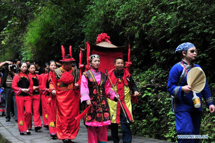 "Working staff from the ""Three Gorges Family"" scenic spot perform a traditional wedding ceremony in Letianxi Town of Yiling District in Yichang City, central China's Hubei Province, Oct. 24, 2012. The ""Three Gorges Family"" is a scenic spot presenting folk customs and traditions of Tujia people. (Xinhua/Zhang Guorong)"