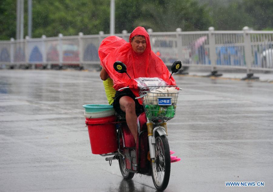 Citizens ride in rain in Sanya, south China's island province of Hainan, Oct. 27, 2012. Son-Tinh, the 23rd tropical storm this year, strengthened to typhoon early Saturday morning and is expected to bring rainstorms and gales to China's southern coastal areas, the country's meteorological authority said Saturday. (Xinhua/Hou Jiansen)
