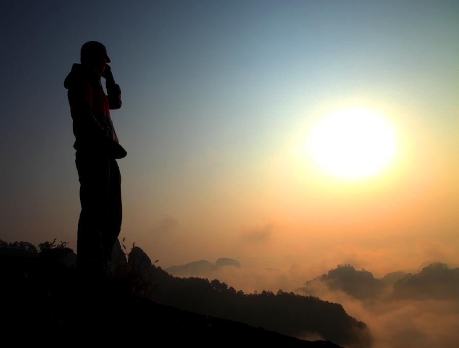 A visitor enjoys the view of sunrise over clouds at a scenery spot of Wuyi Mountain in southeast China's Fujian Province, on Nov. 3, 2012. (Xinhua/Yi Fan)