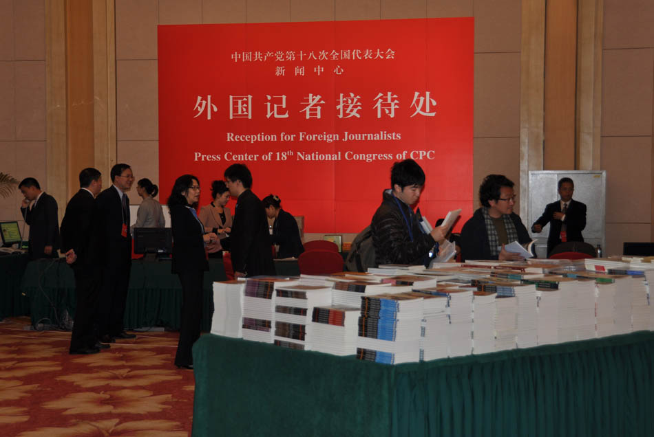 Journalists pick up free books provided by the Press Center of the 18th National Congress of the CPC. (People's Daily Online/Yan Meng)