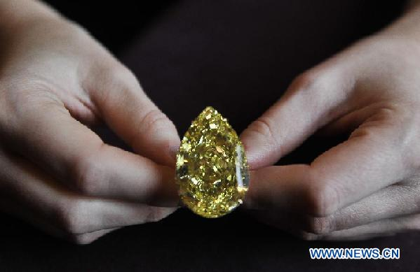 A model presents the Sun-Drop Diamond to meida at a hotel in Geneva, Switzerland, Nov. 9, 2011. The Sun-Drop is a sensational fancy vivid yellow pear-shaped diamond weighing 110.03 carats and is known as the largest pear-shaped fancy vivid yellow diamond in the world. (Xinhua/Yu Yang)