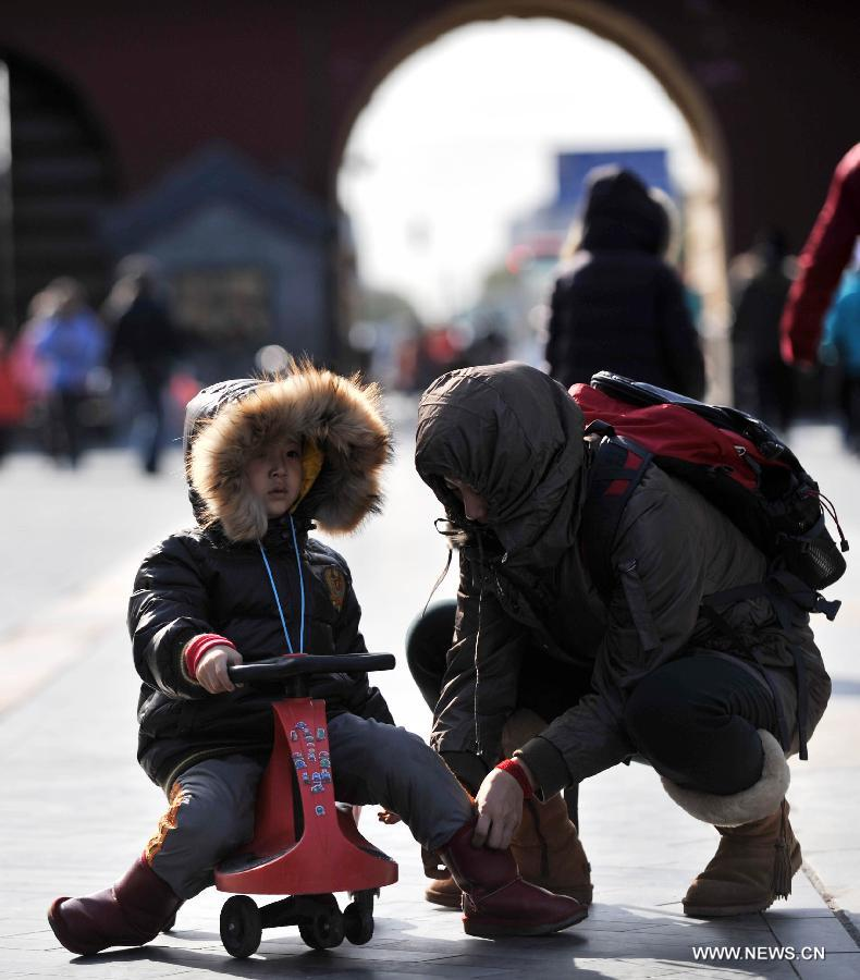 A woman helps a boy wear windproof boots at the Tiantan Park in Beijing, capital of China, Nov. 11, 2012. Beijing experienced windy weather and a sharp fall in temperature on Sunday following a rainfall the previous day. (Xinhua/Li Wen)