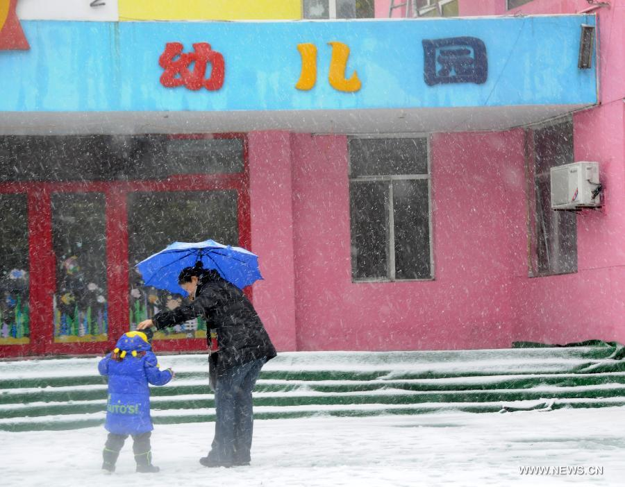 A boy plays in the snow with his parent in a kindergarten in Harbin, capital of northeast China's Heilongjiang Province, Nov. 12, 2012. Many parts of China's northeast region witnessed an extensive snowfall on Sunday and Monday. (Xinhua/Wang Kai)