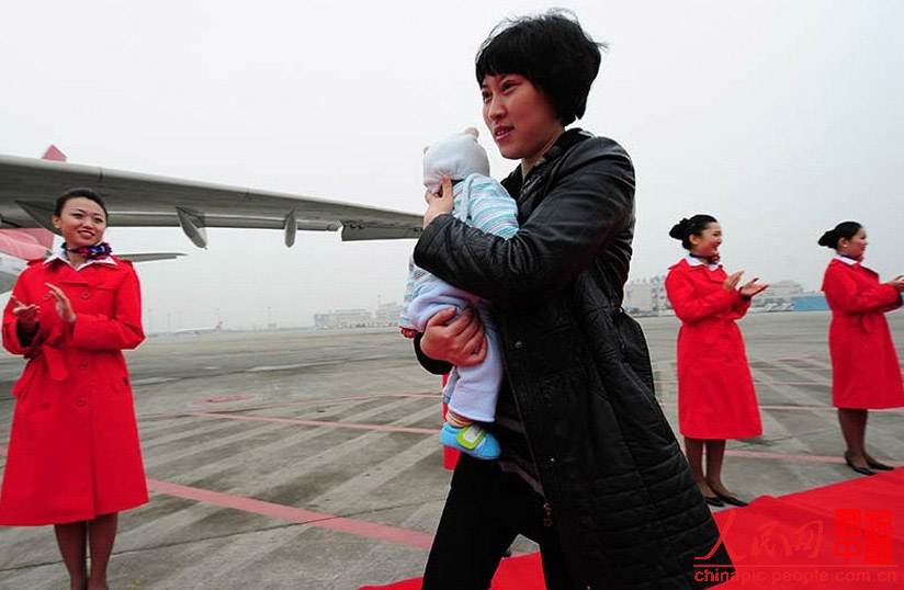 Jiang Min, a deputy to the 18th National Congress of the Communist Party of China from Sichuan, is going to board the plane to Beijing to attend the Congress with her four-month-old daughter. (Photo/ People's Daily Online)