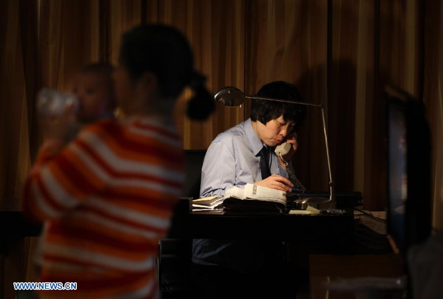 Jiang Min, a delegate to the 18th National Congress of the Communist Party of China (CPC), takes a call at her hotel room while a nanny helps her to take care of the baby in Beijing, capital of China, Nov. 13, 2012.(Xinhua/Jin Liwang)