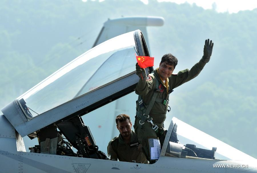 A Pakistani pilot of FC-1 fighter jet greets the audience during the 9th China International Aviation and Aerospace Exhibition in Zhuhai, south China's Guangdong Province, Nov. 13, 2012. (Xinhua/Liu Dawei)