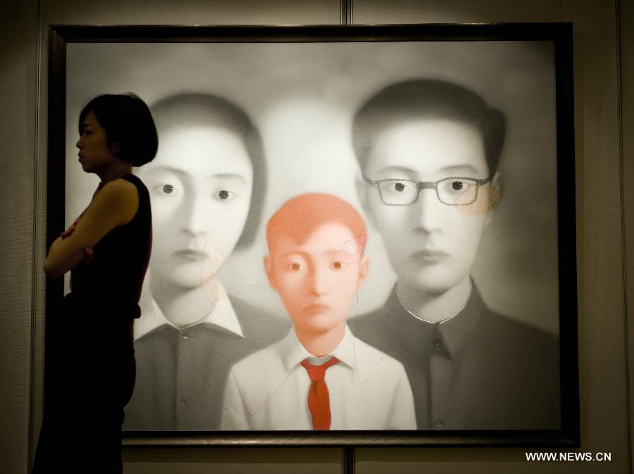 A staff member walks past an oil painting of Zhang Xiaogang on a press conference of the Christie's autumn auction preview event in south China's Hong Kong, Nov. 14, 2012. The auction will be held in Hong Kong from Nov. 24 to Nov. 28. (Xinhua/Lui Siu Wai)