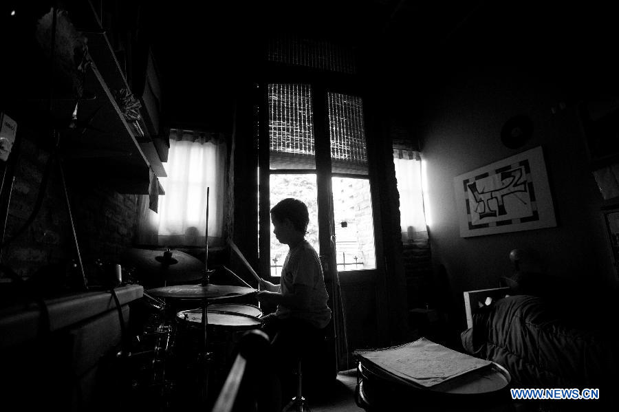 Lisandro Itzcovich, 10 years old, plays drums at home in Buenos Aires, capital of Argentina, on Nov. 19, 2012. (Xinhua/Martin Zabala)