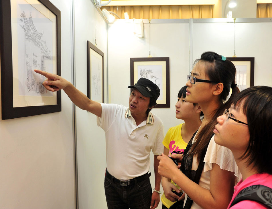 Li Bin (1st L) introduces his works during a solo exhibition held in southeast China's Taiwan, Sept. 17, 2012. (Xinhua/Wu Ching-teng)