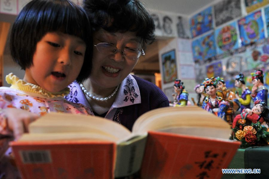 "Li Lingxiu tells the storis of ""A Dream of the Red Chamber"" to a girl in Lanzhou, capital of northwest China's Gansu Province, Nov. 20, 2012. The retired worker Li Lingxiu created 30 clay sculptures of characters in the ancient Chinese novel classic ""A Dream of the Red Chamber"". (Xinhua/Chen Bin)"