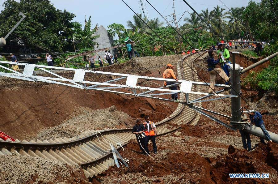 Staff members try to fix railway and electric wires broken in a landslide in Bogor, Indonesia, Nov. 22, 2012. Landslide caused by rainfall Wednesday night destroyed rails and led to the cancel of 98 flights. (Xinhua/Dwi)