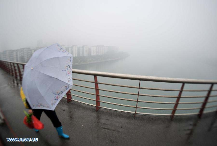 A citizen walks in the fog-shrouded Liuzhou City, southwest China's Guangxi Zhuang Autonomous Region, Nov. 25, 2012. (Xinhua/Li Hanchi)