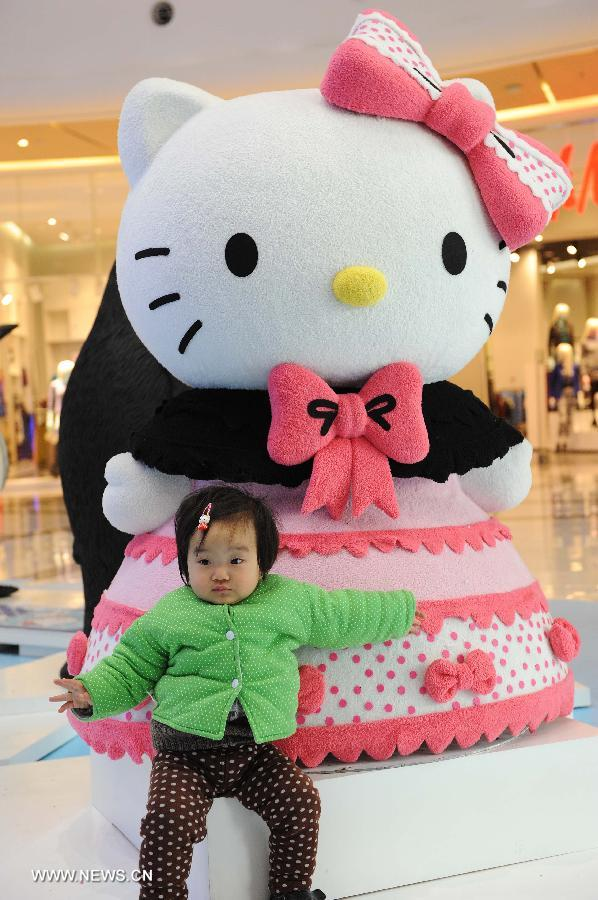 A child poses for pictures in front of a Hello Kitty in the Joy City in east China's Shanghai Municipality, Nov. 26, 2012. A big Hello Kitty exhibition themed on Hello Kitty's exploration in the polar regions would last from Nov. 24, 2012 to Feb. 24, 2013 in Shanghai. (Xinhua/Lai Xinlin)
