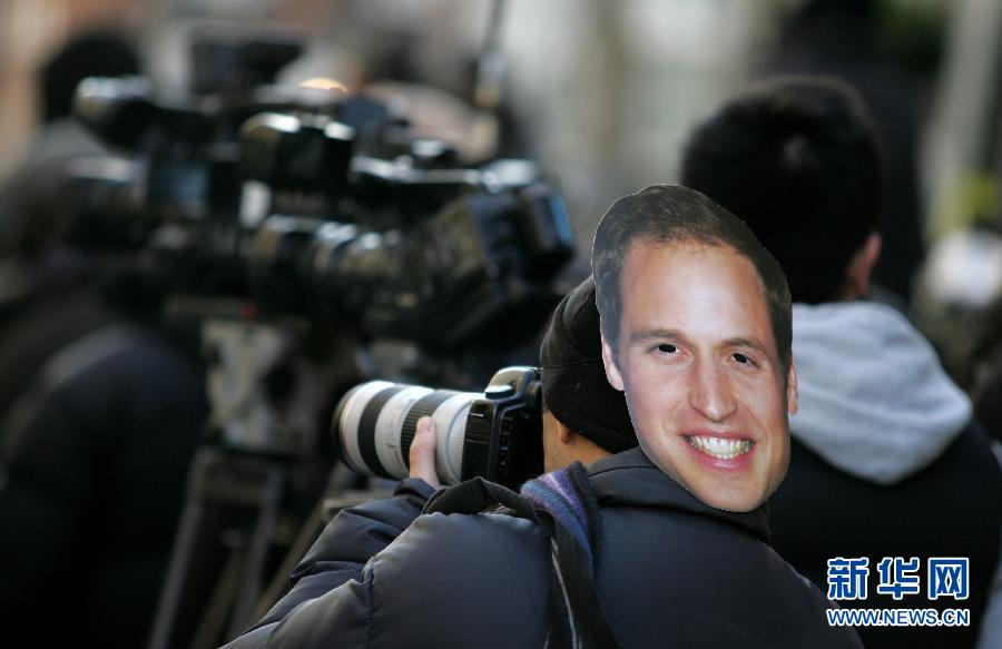 A photographer takes pictures with an image of Prince William on his head outside King Edward VII hospital, where Catherine, the Duchess of Cmabridge, hospitalizes for her sickness due to pregnancy, in central London of Britain, on Dec. 4, 2012. British royal Prince William and his wife Catherine are expecting their first child. (Xinhua/Bimal Gautam)