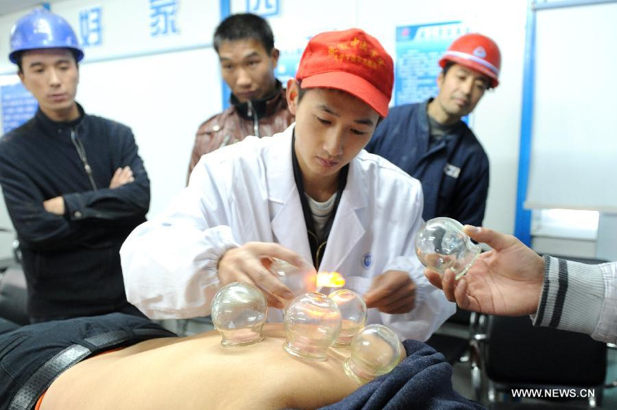 A volunteer from Anhui Chinese Traditional Medicine Institute implements cupping therapy on a migrant worker in Hefei, capital of east China's Anhui Province, Dec. 5, 2012. Many Chinese volunteers make their contributions to the society on Wednesday, to mark the International Volunteer Day, which is an international observance designated by the United Nations since 1985. (Xinhua/Liu Junxi)