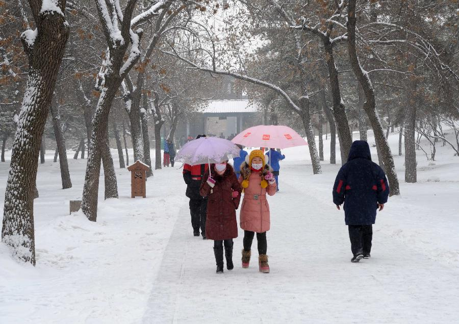 Visitors tour the Summer Resort in snow in Chengde, north China's Hebei Province, Dec. 14, 2012. Heavy snow battered parts of northern China these days. (Xinhua/Wang Kun)
