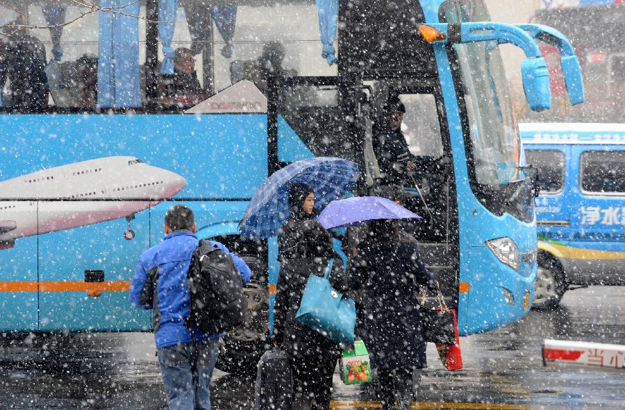 Passengers board on a bus in Qingdao, east China's Shandong Province, Dec. 18, 2012. The temperature will linger around zero degree centigrade starting on Dec. 20, according to the local meterological authority. (Xinhua/Li Ziheng)