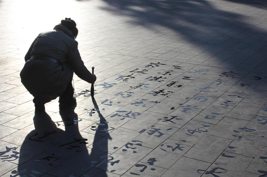 "Photo ""Shadows"" shows a woman working on her calligraphy at the Temple of Heaven. A lot of people do this across Beijing's parks, creating both a special scenery as well as atmosphere. (China.org.cn/Guillet Raphael)"