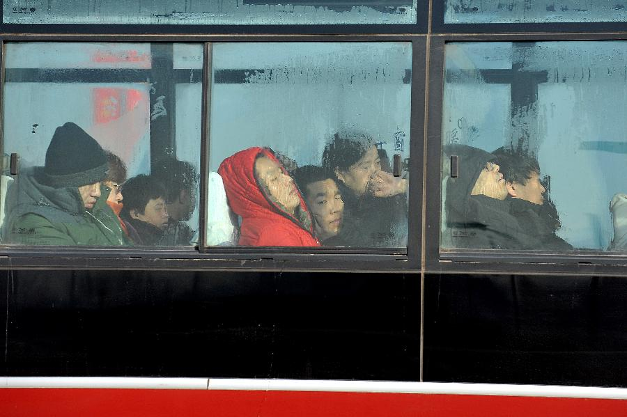 Passsgngers dressing in warm clothes sit in a bus in Taiyuan, north China's Shanxi Province, Jan. 5, 2013. Jan. 5 is the Slight Cold, the 23rd solar term according to the traditional Chinese lunar calendar, ushering in the coldest period in China. (Xinhua/Zhan Yan)
