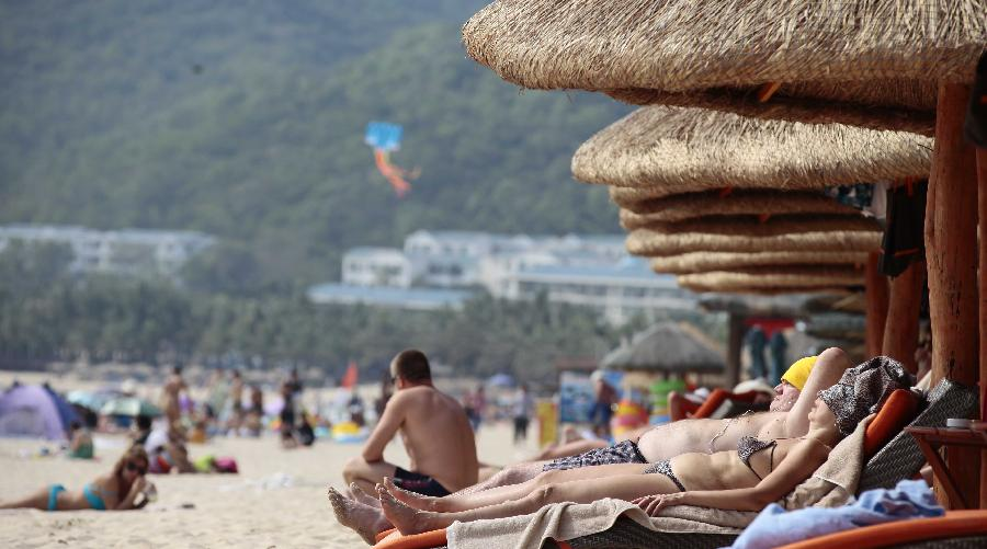 Tourists enjoy sunbath at a beach in Sanya, a popular winter tourism destination in south China's Hainan Province, Jan. 5, 2013. (Xinhua/Chen Wenwu)