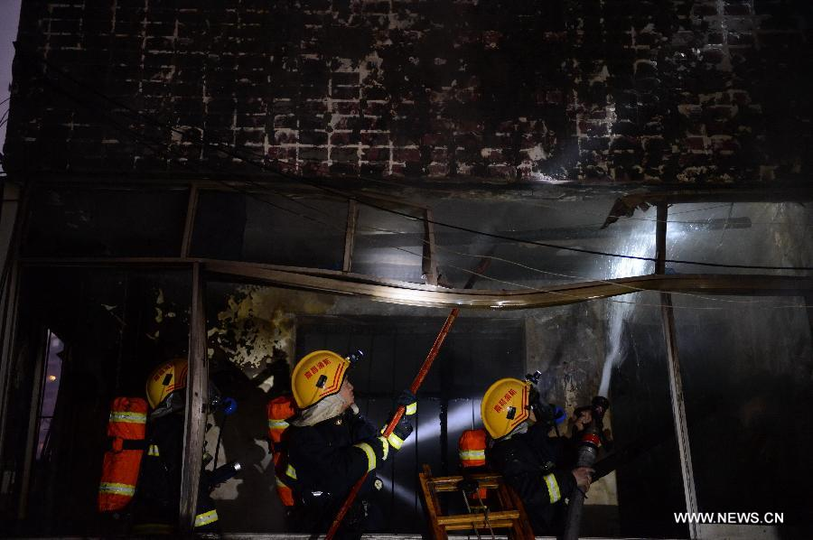 Firefighters extinguish fire at a residential building on the Honggu Road in Nanchang, capital of east China's Jiangxi Province, Jan. 6, 2013. A fire broke out on the first floor of the building on Sunday. No casualty is reported at present and the cause is still under investigation. (Xinhua/Zhou Mi)