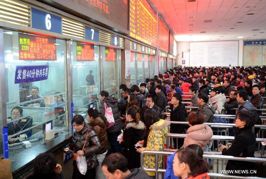 People line to buy railway tickets at Nanchang Railway Station in Nanchang, capital of east China's Jiangxi Province, Jan. 9, 2013. The tickets for the upcoming Spring Festival rush period can be purchased at ticket offices and agencies since Jan. 9. The 40-day 2013 Spring Festival travel rush will start on Jan. 26. The Spring Festival for family reunions begins from the first day of the first month of the traditional Chinese lunar calendar, or Feb. 10, 2013. (Xinhua/Zhou Ke)