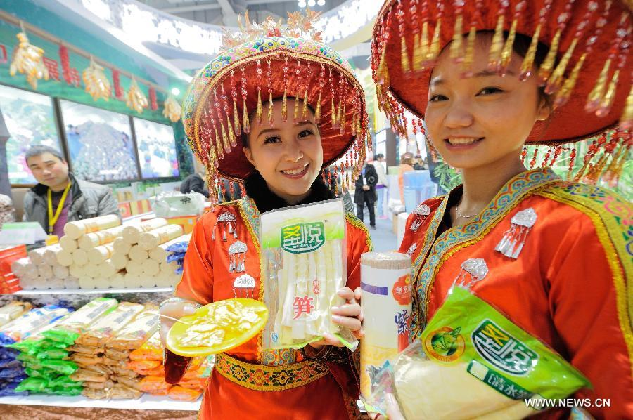 Saleswomen show products at the 12th Western China (Chongqing) International Agricultural Products Fair in southwest China's Chongqing, Jan. 10, 2013. The fair kicked off here on Thursday. (Xinhua/Li Jian)