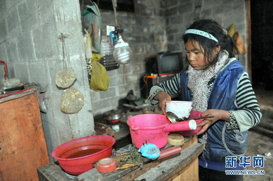 Li Azuo clears up the dishes after meal in a village in Guangxi on Jan. 8, 2013. (Xinhua/Zhou Hua)