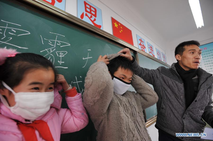 Two students demonstrate wearing masks under a guidance of a teacher in an indoor physical education class as the outdoor sports activities for primary and middle schools were ordered to be halted due to heavy air pollution in Hupo Shanzhuang Elementary School in Hefei, capital of east China's Anhui Province, Jan. 14, 2013. Emergency response measures were adopted in many Chinese cities, where the air has held excessive levels of major pollutants in the past few days due to prolonged fog and smog. Heavy fog has caused highway closures and flight delays in several provinces. The elderly, children and those suffering from respiratory and cardiovascular diseases are advised to stay indoors to reduce exposure to polluted air. (Xinhua/Yang Xiaoyuan)