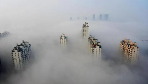 Skyscrapers are partly seen amid thick fog in Suzhou