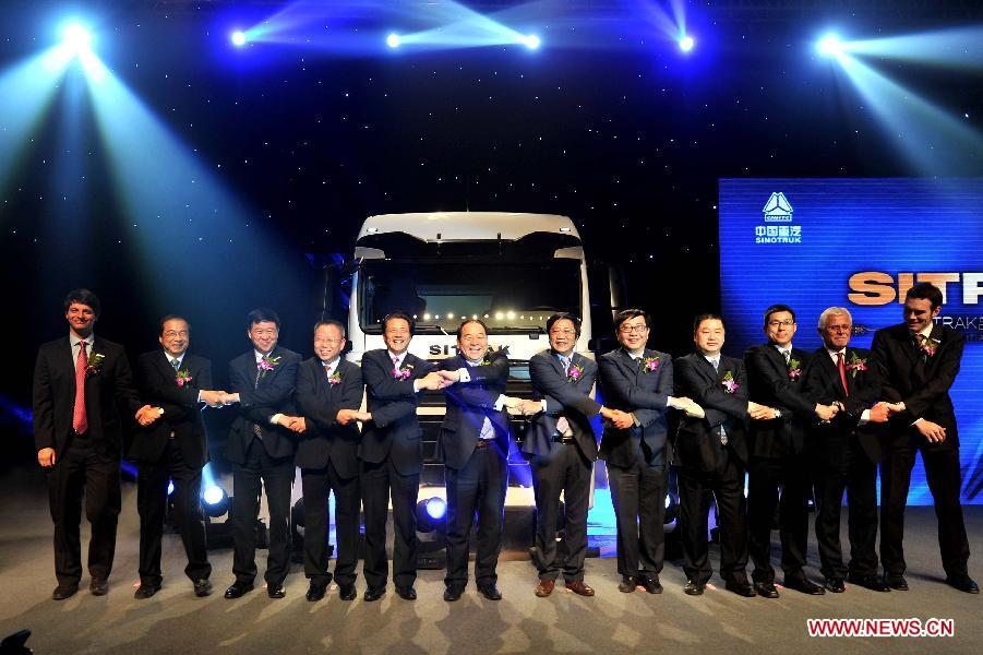 Guests pose for photos in front of the first SITRAK duty truck during the off assembly line ceremony at the China National Heavy Duty Truck Group (CNHTC) Jinan Commercial Vehicle Co. Ltd, in Jinan, capital of east China's Shandong Province, Jan. 17, 2013. As advanced heavy duty truck produced by CNHTC in cooperation with MAN Truck & Bus AG from Germany (MAN), the SITRAK duty truck was off assembly line on Thursday. (Xinhua/Xu Suhui)