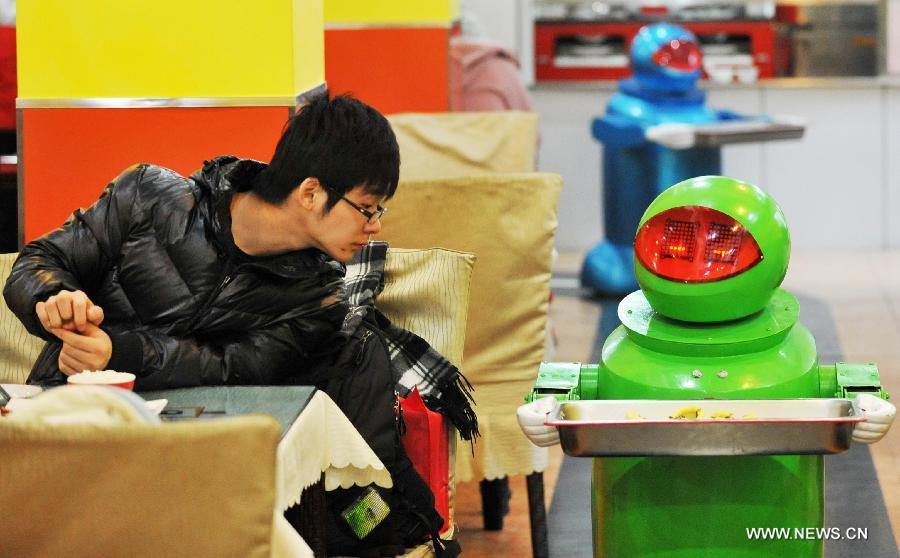 A customer watches a robot serving dishes in a robot themed restaurant in Harbin, capital of northeast China's Heilongjiang Province, Jan. 18, 2013. Opened in June of 2012, the restaurant has gained fame by using a total of 20 robots to cook meals, deliver dishes and greet customers. (Xinhua/Wang Jianwei)