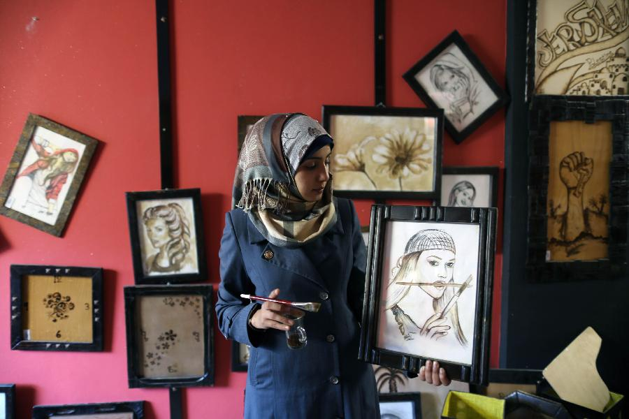 Palestinian artist Salwa Sbakhi paints using coffee at her studio in Gaza City, on Jan 22, 2013. Sbakhi has studied fine arts at Al-Aqsa University in Gaza and participated in numerous local exhibitions. (Xinhua/Wissam Nassar)