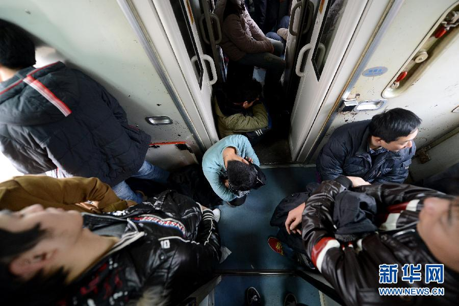 A man without seat crouches in the narrow corridor of a training traveling toward Qingdao, Jan. 19, 2013. (Photo/Xinhua)