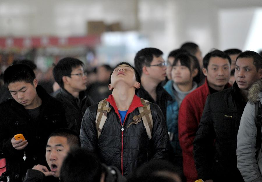 A student is seen relaxing in the waiting hall of the Hefei Train Station in Hefei, capital of east China's Anhui Province, Jan. 23, 2013. Hefei witnessed a student travel peak as winter holidays started in recent days. (Xinhua/Guo Chen)