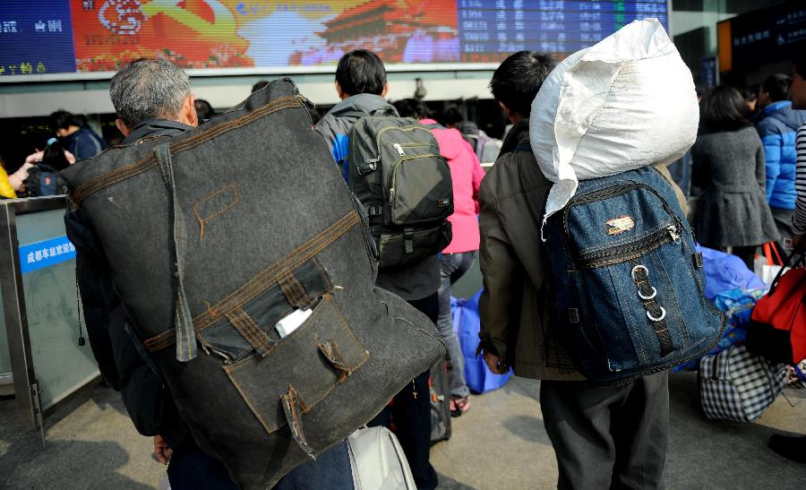 Passengers carry their luggage on the square of the train station in Chengdu, capital of southwest China's Sichuan Province, Jan. 24, 2013. As the spring festival approaches, more than more people started their journey home. (Xinhua/Xue Yubin)