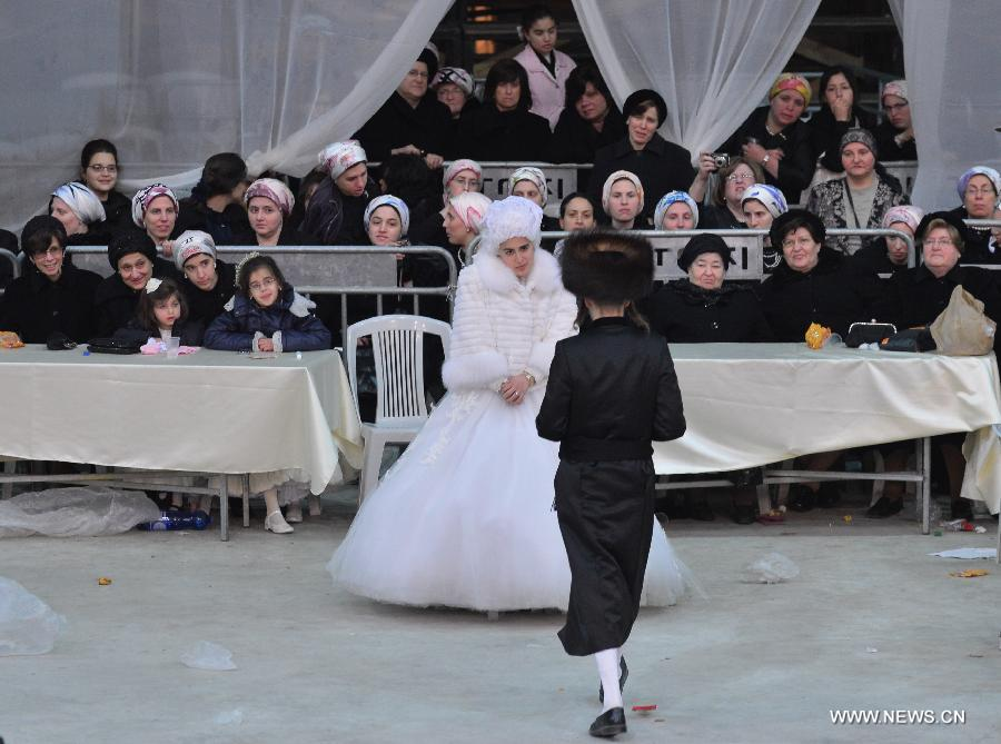 The groom Moshey Chaim walks to invite his bride, the first granddaughter of Grand Rabbi of the Satmar hassidic dynasty Rabbi Zalman Leib Teitelbaum, to dance during their wedding in Israeli town of Beit Shemesh, on Jan. 24, 2013. The wedding was held here from the evening of Jan. 23 to the morning of Jan. 24. Some 5,000 guests attended the traditional Jewish wedding. (Xinhua/Yin Dongxun)