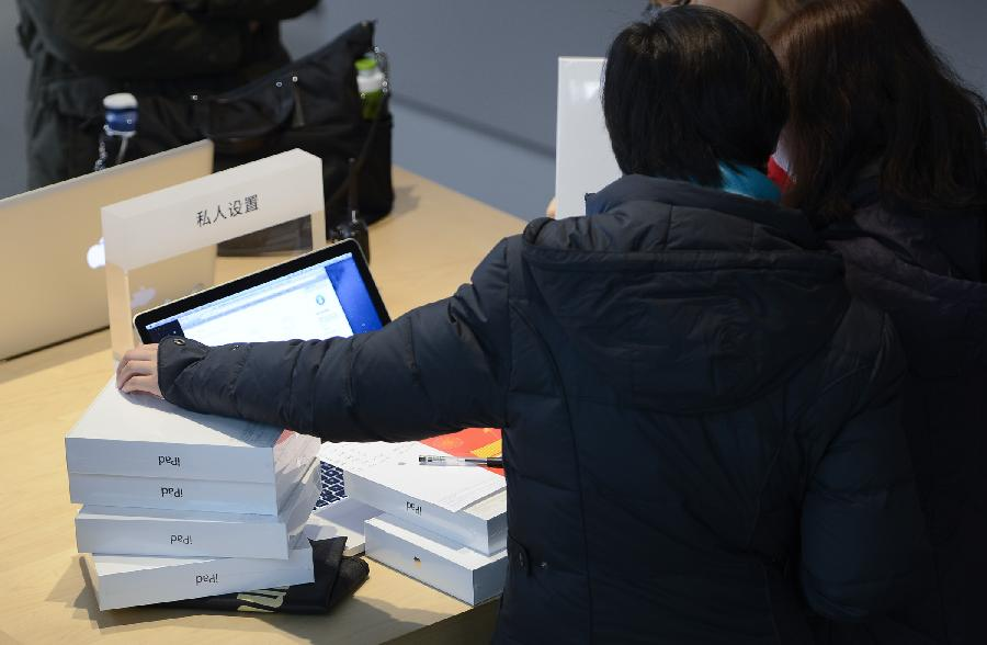 Customers choose apple products at Wangfujin Apple Store in Beijing, capital of China, Jan. 25, 2013. Apple Store held a sales activity on Friday, during which customers could enjoy special pricing online and at Apple retail stores on apple products. (Xinhua/Qi Heng)