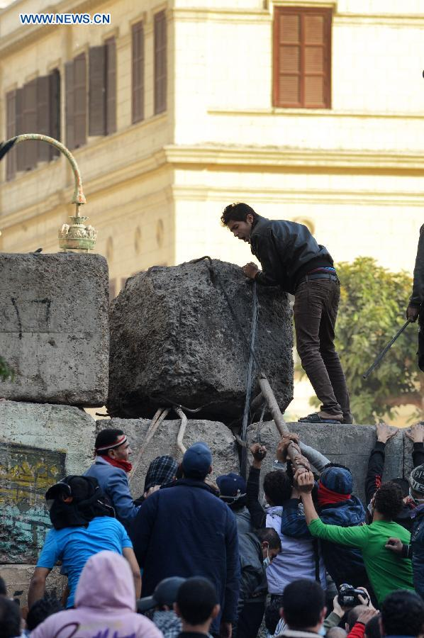 Protesters tear down the cement wall set up by police near Cairo's Tahrir Square on Jan. 25, 2013, during a massive demonstrations held nationwide to mark the second anniversary of the 2011 unrest that toppled former president Hosni Mubarak. (Xinhua/Li Muzi)