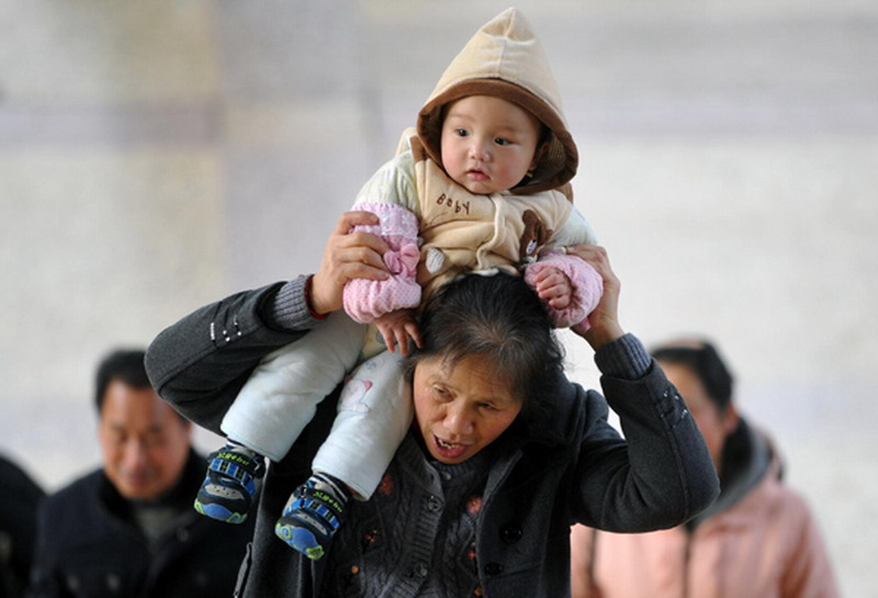 A woman carries a baby on her shoulder at Changsha Railway Station, Jan 26, 2013.  (Photo/Xinhua)