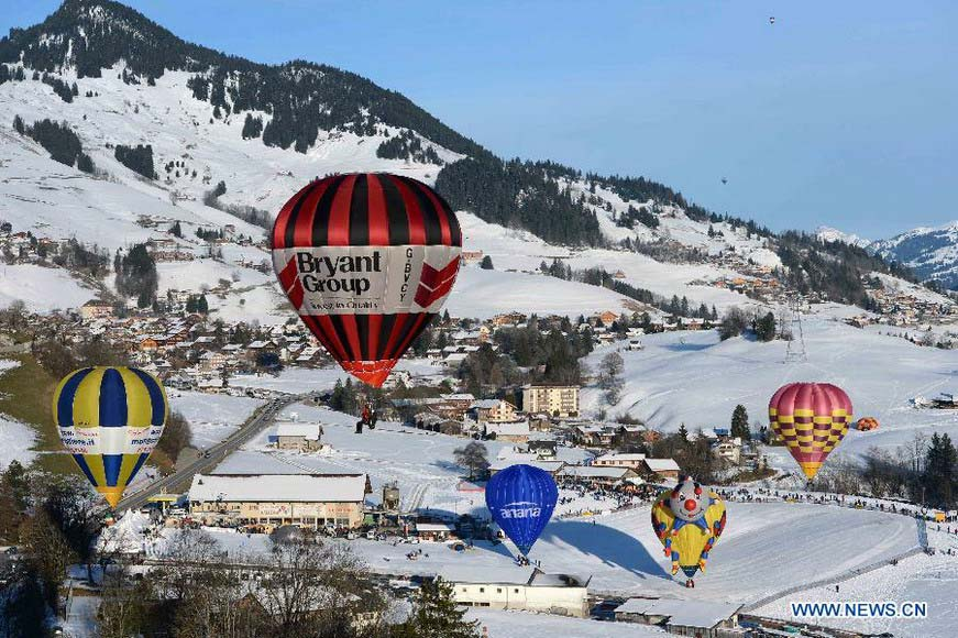 Balloons fly over Chateau-d'Oex, Switzerland, Jan. 26, 2013. The 9-day 35th International Balloon Festival kicked off here on Saturday with the participation of over 80 balloons from 15 countries and regions. (Xinhua/Wang Siwei)